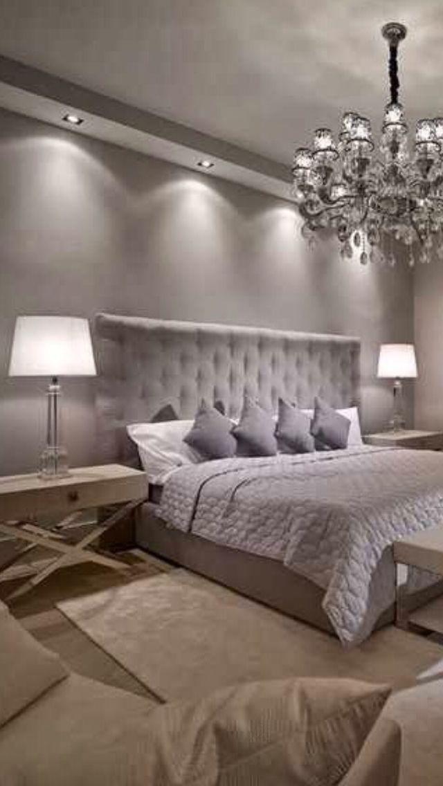 Luxury Bedroom design. Luxury chandelier. White table lamp. Silver bed. Modern m...