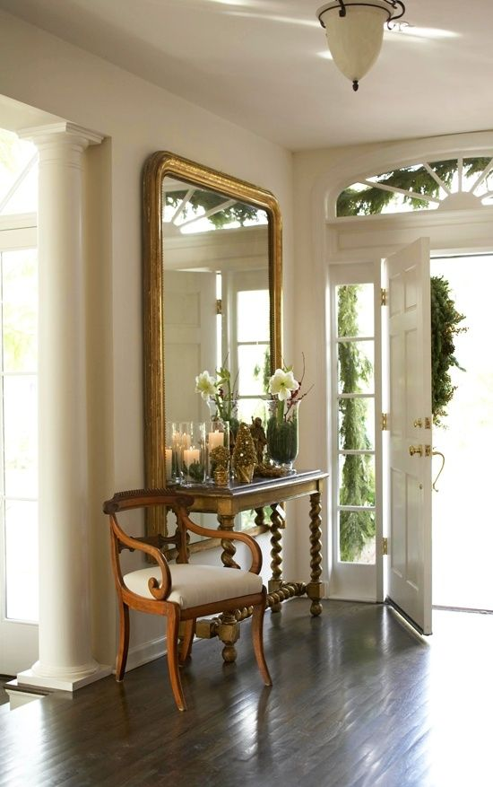 An oversized gilded mirror establishes a beautiful display in this foyer - Tradi...