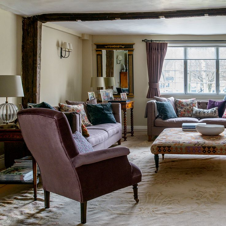Country living room with purple velvet armchair. Mirror and accessories.