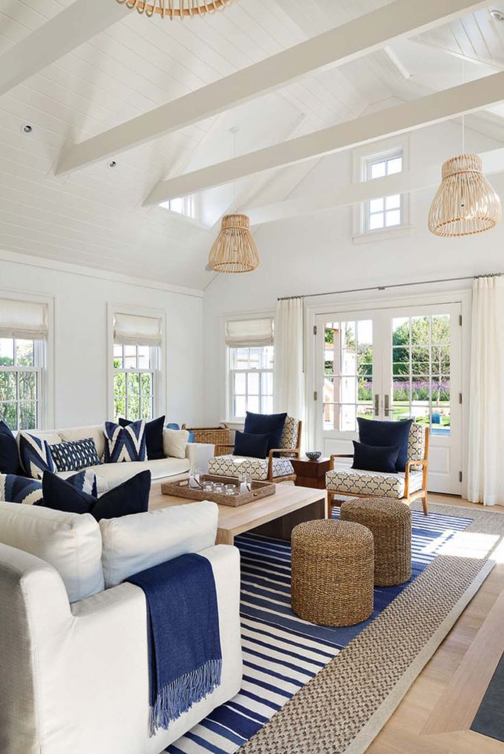 coastal white and blue living room with layered rugs...