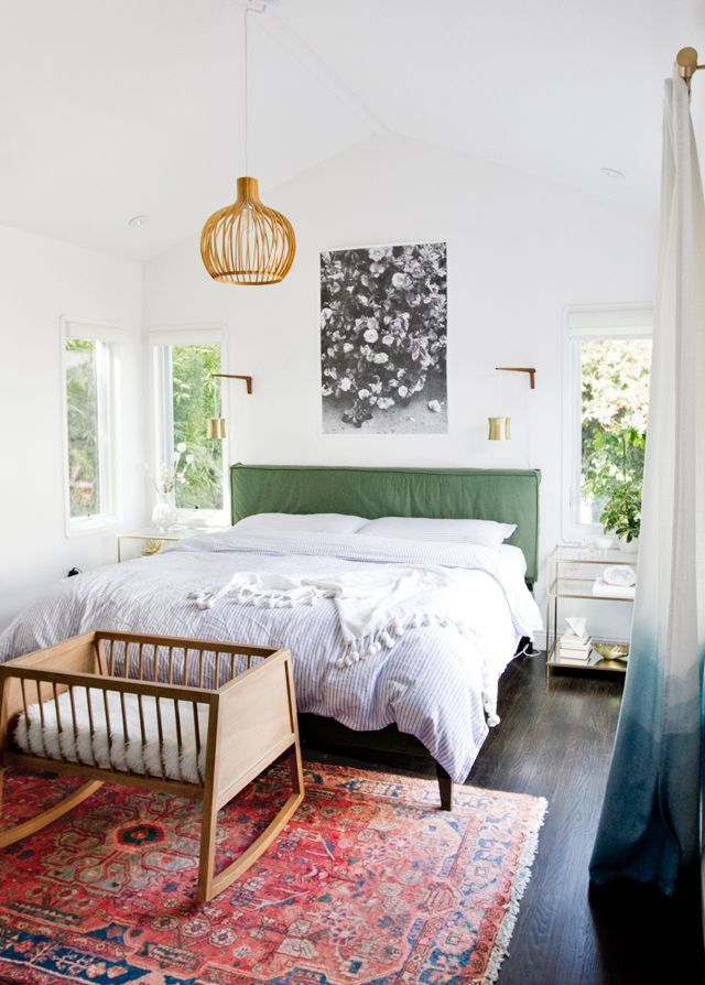 Colorful midcentury modern bedroom with a pink rug, green headboard and brass wa...