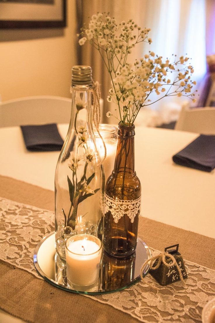 Wine bottle vases sitting atop of a round mirror with votive candle rests on a b...
