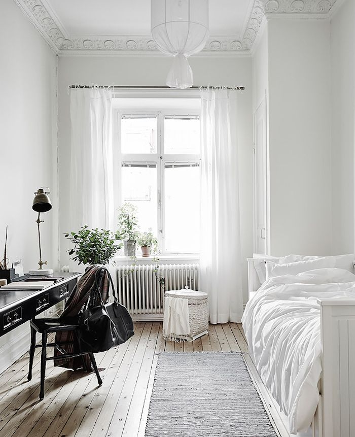 Bedroom with workspace: pale limewashed timber floorboards, white wooden daybed,...