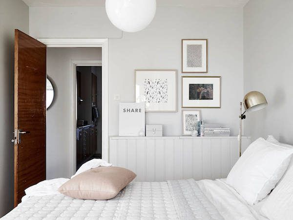 the grey walls, brass reading lamp, gallery wall and a Hay polygon quilt in a sw...