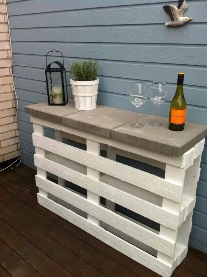 2 pallets + 3 pavers + white paint = a great outdoor shelf, bar or garden table....