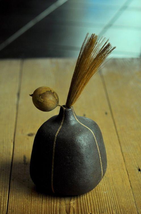 brown square pot with dried plants. by yoko komae.