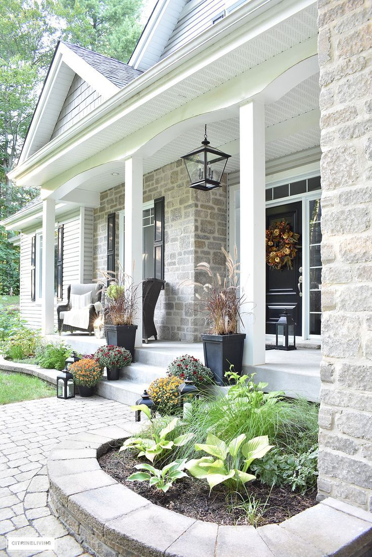 A simple and elegant front porch decorated for Fall with seasonal flowers in aut...