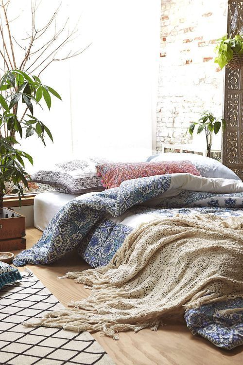mattress on floor, but styling and plants make it look luxurious and comfortable...