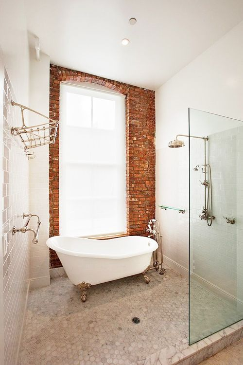 Simple Bathroom With Freestanding Tub And Brick Wall.