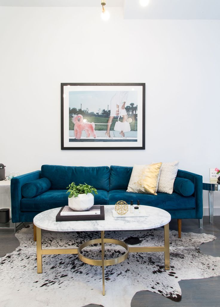 Space with a blue velvet sofa, cowhide rug, and a marble coffee table