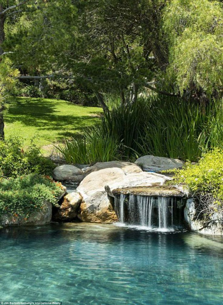 A waterfall off to the side completes the serene landscape of the pool area, pla...
