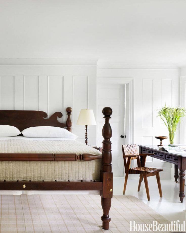 Strong-lined furnishings in rich browns lend drama to a white master bedroom. A ...