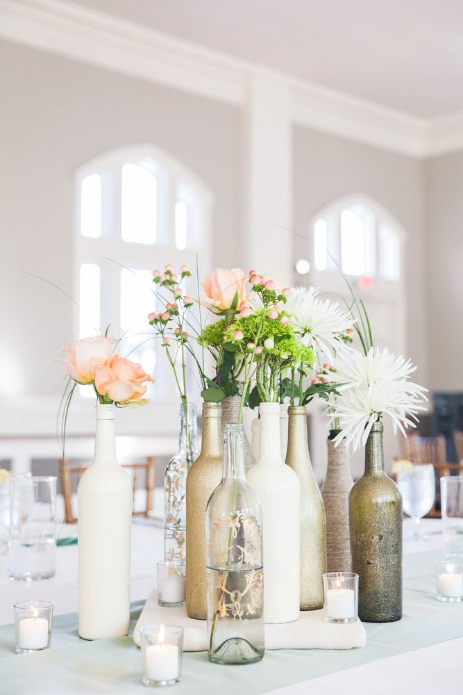 Wine bottle centerpieces painted in gold or white with an assortment of flowers....