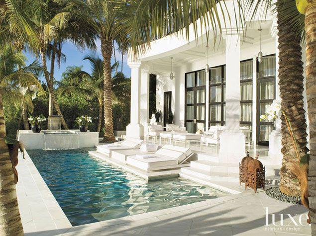 White alabaster stone covers this patio, extending into the pool making lounging...