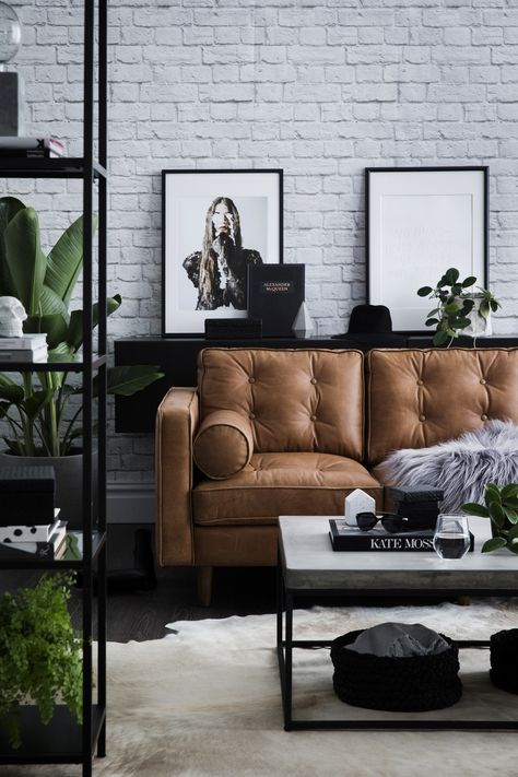 modern interior with white brick walls black elements and a tan leather sofa - l...